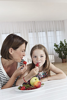 Germany, Munich, Mother and daughter eating fruits, smiling - SKF000654