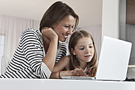 Germany, Munich, Mother and daughter using laptop, smiling - SKF000657