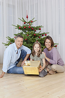 Germany, Munich, Family sitting by christmas tree with gift, smiling, portrait - SKF000663