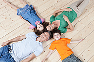 Germany, Munich, Parents and children lying on floor, smiling - SKF000687