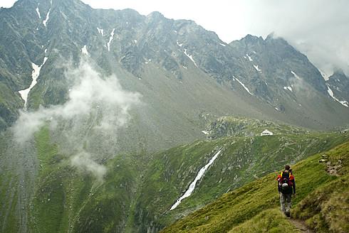 Austria, Tirol, Mid adult man walking to alpine hut - KAF000002