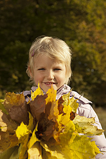 Germany, Bavaria, Girl holding leaves, smiling, portrait - RNF000775