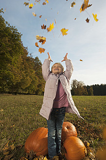 Germany, Bavaria, Girl playing with leaves, smiling - RNF000781