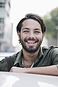 Germany, Cologne, Young man near car, smiling, portrait - FMKF000353
