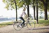Germany, Cologne, Young woman on bicycle, smiling, portrait - FMKF000374