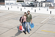 Germany, Cologne, Young couple with shopping bags, smiling - FMKF000395