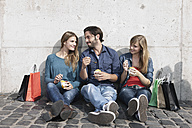 Germany, Cologne, Young man and woman with ice cream and shopping bags, smiling - FMKF000428
