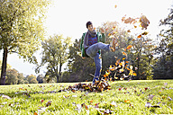 Germany, Cologne, Young man playing with leaves in park, smiling - RHF000005