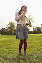 Germany, Cologne, Young woman with cell phone in park - RHF000008