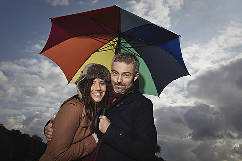 Germany, Cologne, Couple with umbrella, smiling, portrait - RHF000047