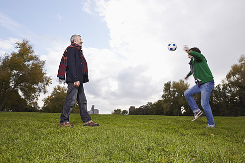 Germany, Cologne, Man playing soccer in park - RHF000050