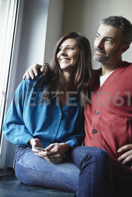 Germany, Cologne, Couple at window with cell phone, smiling - RHF000071