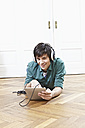 Germany, Cologne, Young man with digital tablet and headphones, smiling, portrait - RHF000074
