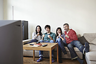 Germany, Cologne, Man and woman watching TV, smiling - RHF000092