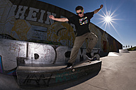 Germany, North Rhine-Westphalia, Duisburg, Skateboarder performing trick on ramp at skateboard park - KJF000161