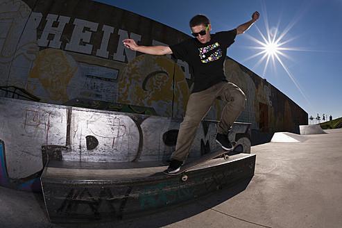 Germany, North Rhine-Westphalia, Duisburg, Skateboarder performing trick on ramp at skateboard park - KJF000161