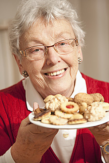 Senior woman with christmas cookies, smiling, portrait - RIMF000100