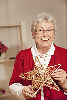 Senior woman holding star during christmas, smiling, portrait - RIMF000101