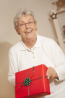 Senior woman with gift box during christmas, smiling, portrait - RIMF000103