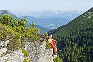 Austria, Salzburg, Hiker sitting on rock, portrait - HHF003769