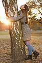 Germany, Berlin, Wandlitz, Mid adult woman hugging tree - WESTF018340