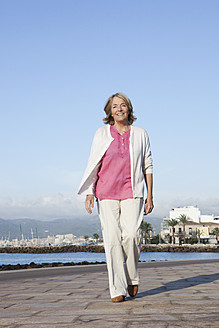Spain, Mallorca, Senior woman walking along sea shore, smiling - SKF000781