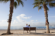 Spain, Mallorca, Senior couple sitting on bench at sea shore - SKF000805