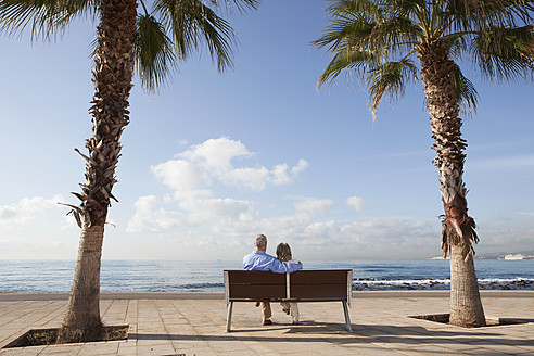 Spain, Mallorca, Senior couple sitting on bench at sea shore - SKF000805