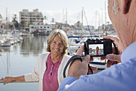 Spain, Mallorca, Palma,Senior man taking picture of woman at harbour - SKF000817