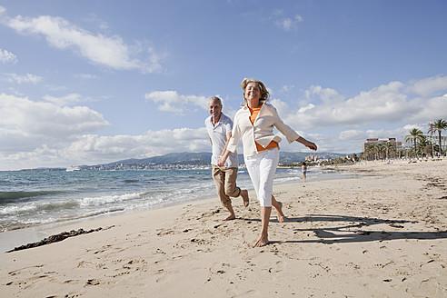 Spain, Mallorca, Senior couple running along beach, smiling - SKF000838