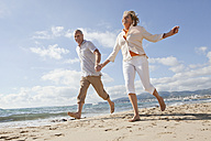 Spain, Mallorca, Senior couple running along beach, smiling - SKF000841