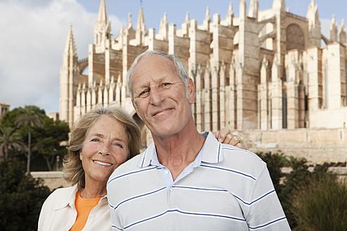 Spain, Mallorca, Palma, Senior couple smiling with Cathedral Santa Maria, portrait - SKF000862