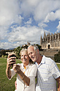 Spain, Mallorca, Palma, Senior couple smiling taking picture with Cathedral Santa Maria, portrait - SKF000868