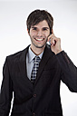 Businessman using cell phone, smiling, portrait - MAEF004238