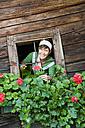 Austria, Salzburg, Flachau, Young woman watering flowers through window, smiling, portrait - HHF003864
