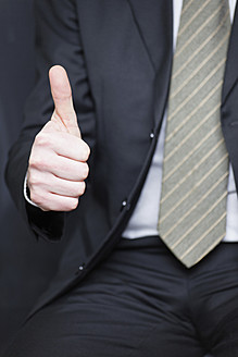 Germany, Businessman showing thumbs up sign, close up - ANBF000061