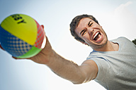 Spain, Mallorca, Young man holding beach volley ball - MFPF000005