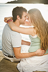 Spain, Mallorca, Couple sitting on beach, smiling - MFPF000014