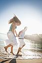 Spain, Mallorca, Couple running along beach - MFPF000017