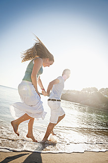 Spain, Mallorca, Couple running along beach - MFPF000017