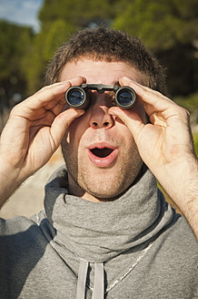 Spain, Mallorca, Young man looking through binocular - MFPF000020