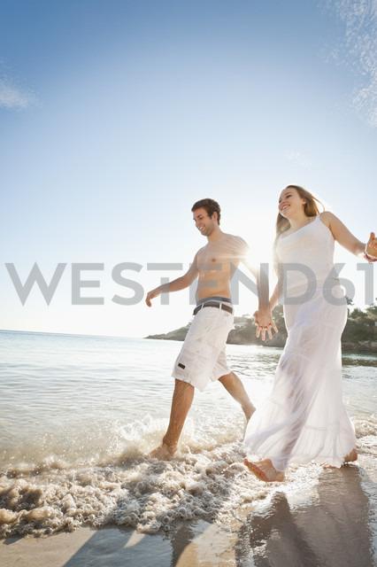 Spain, Mallorca, Couple running along beach - MFPF000023