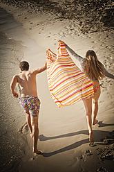 Spain, Mallorca, Couple running along beach - MFPF000026