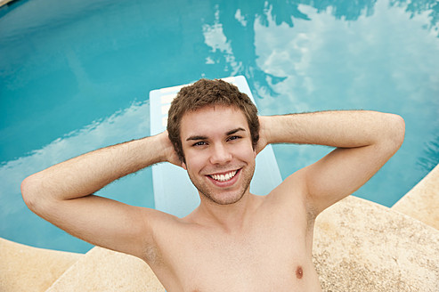 Spain, Mallorca, Young man lying on diving board, smiling, portrait - MFPF000035