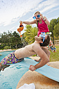 Spain, Mallorca, Couple playing on swimming pool - MFPF000038