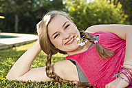 Spain, Mallorca, Teenage girl lying in grass, smiling, portrait - MFPF000047