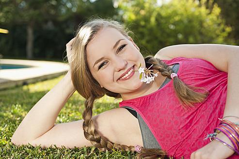Spain, Mallorca, Teenage girl lying in grass, smiling, portrait - MFPF000047