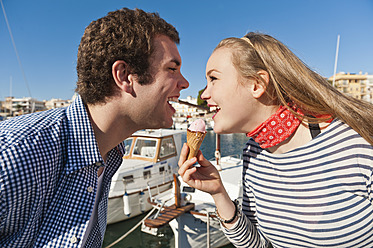 Spain, Mallorca, Couple eating ice cream at harbour, smiling - MFPF000059