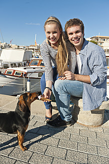Spain, Mallorca, Couple feeding ice cream to stray dog, smiling, portrait - MFPF000062