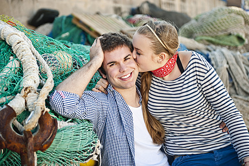Spain, Mallorca, Couple at harbour with fishing nets, smiling - MFPF000065